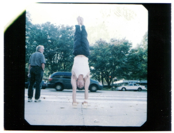 Circus acrobat doing a handstand in front of 77 Mass Ave (MIT)