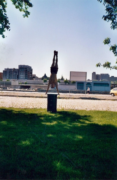 Circus acrobat does a handstand on a trashcan in the old port while a student at the National Circus School of Montreal