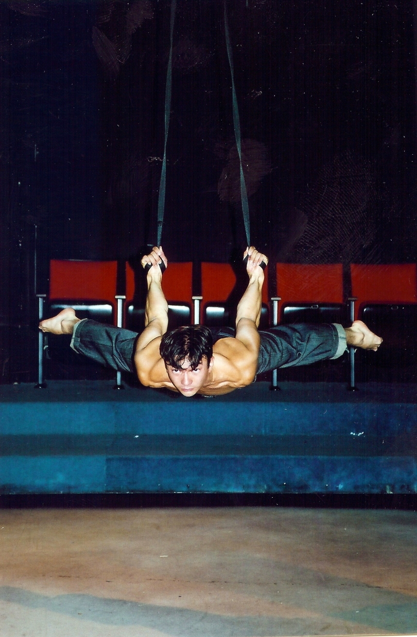 Circus acrobat doing a planche on straps