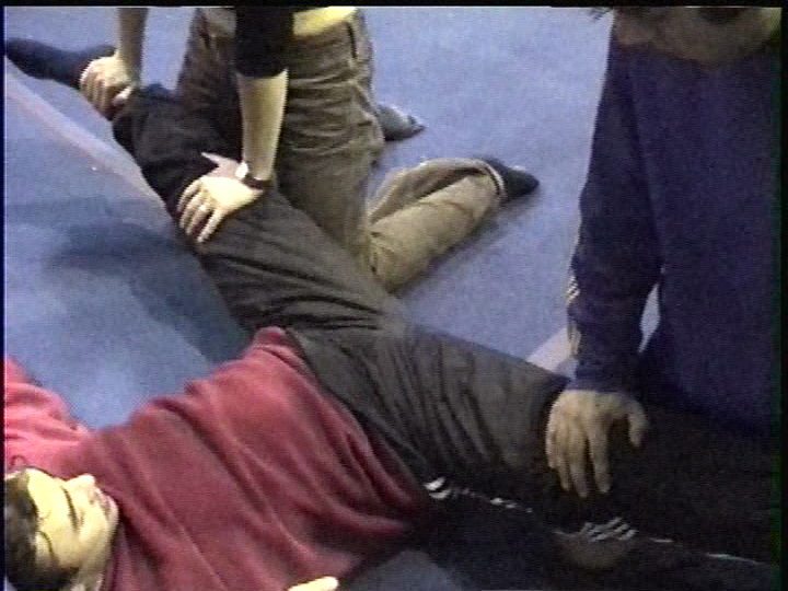 Circus school student getting stretched for his center splits