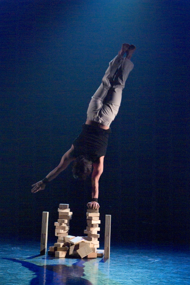 Circus acrobat in a one armed handstand