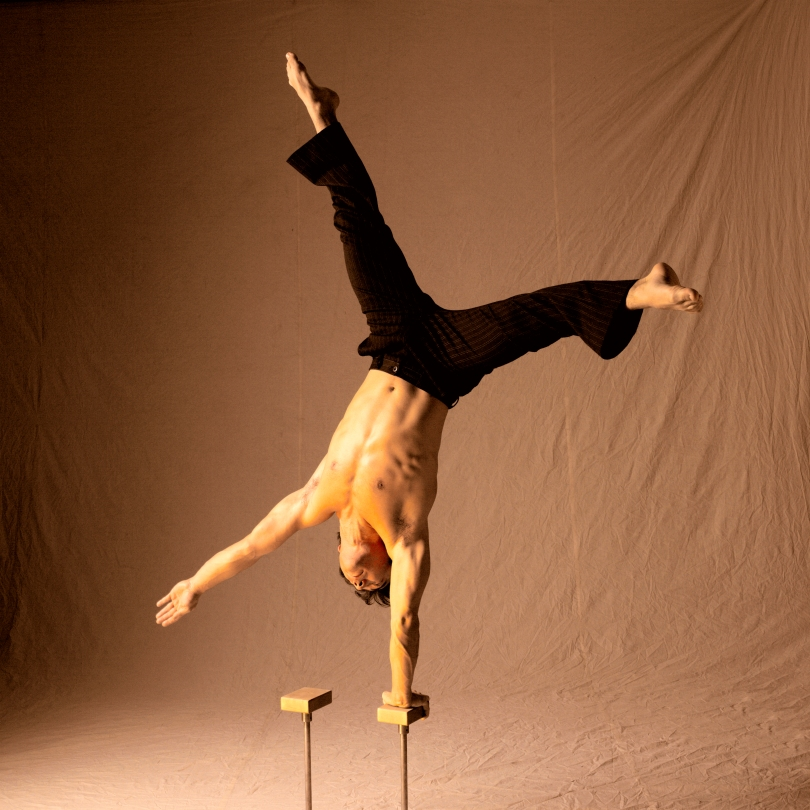 Circus acrobat holding a one-armed handstand at the National Circus School of Montreal
