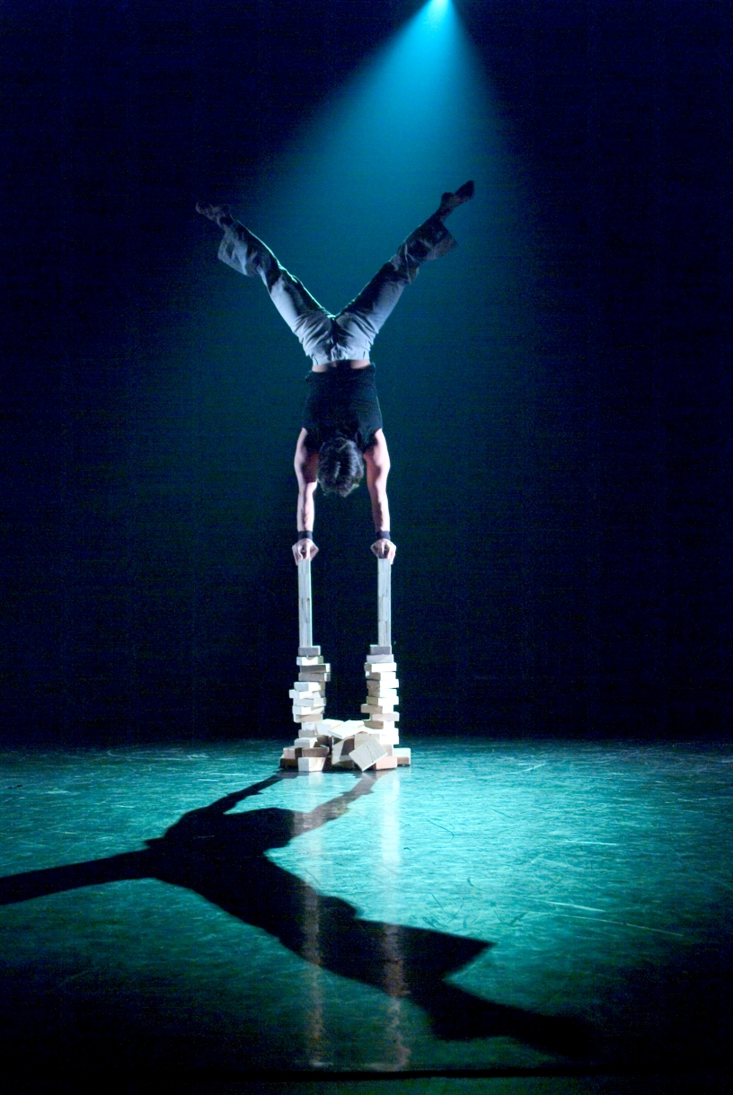 Circus acrobat doing handstand on a tower of blocks