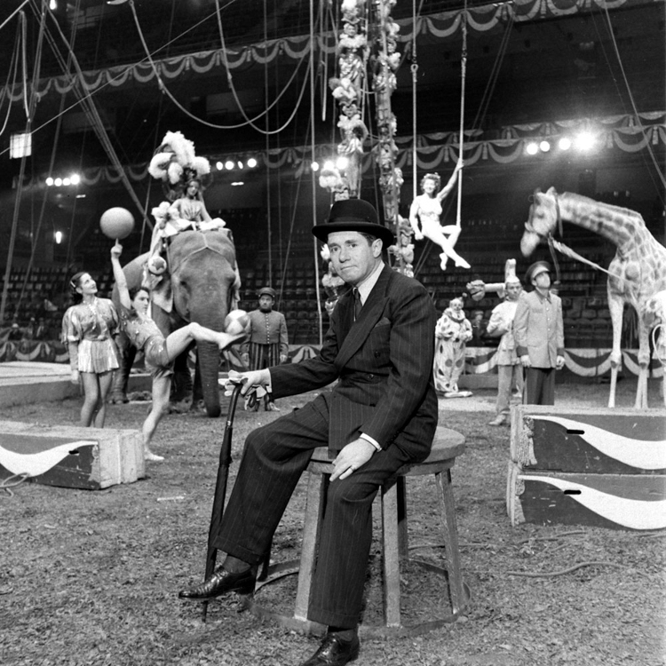 Circus ringmaster in front of circus acrobats under a travelling big top